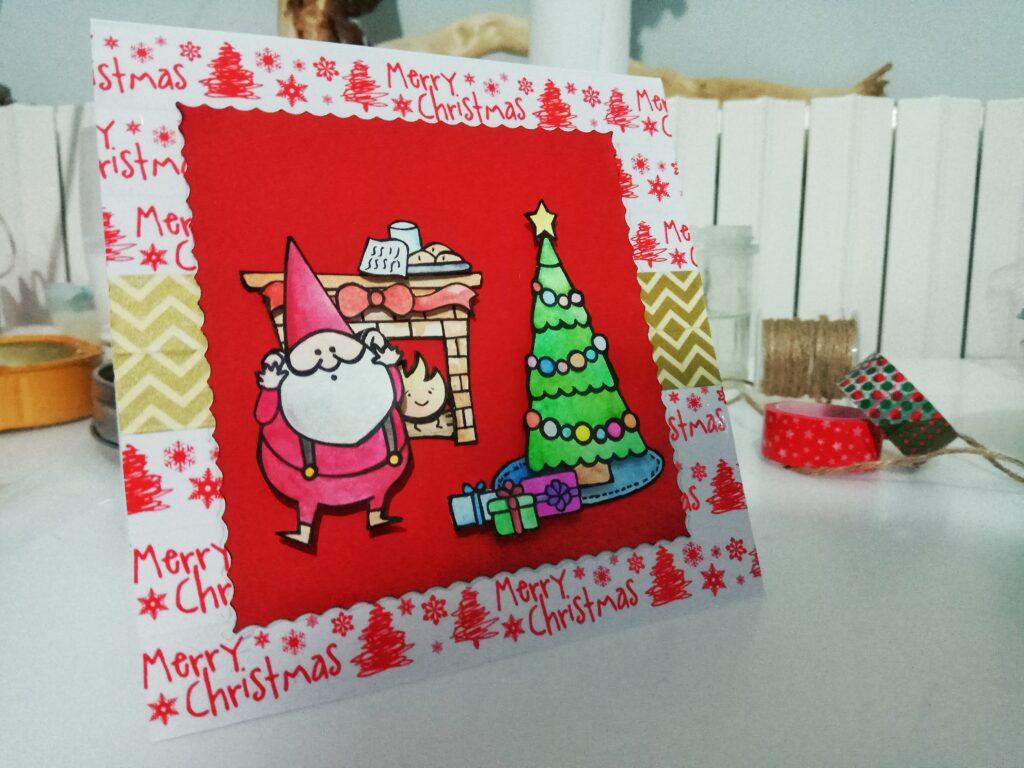 Card natalizia con Babbo Natale, caminetto e albero con strenne