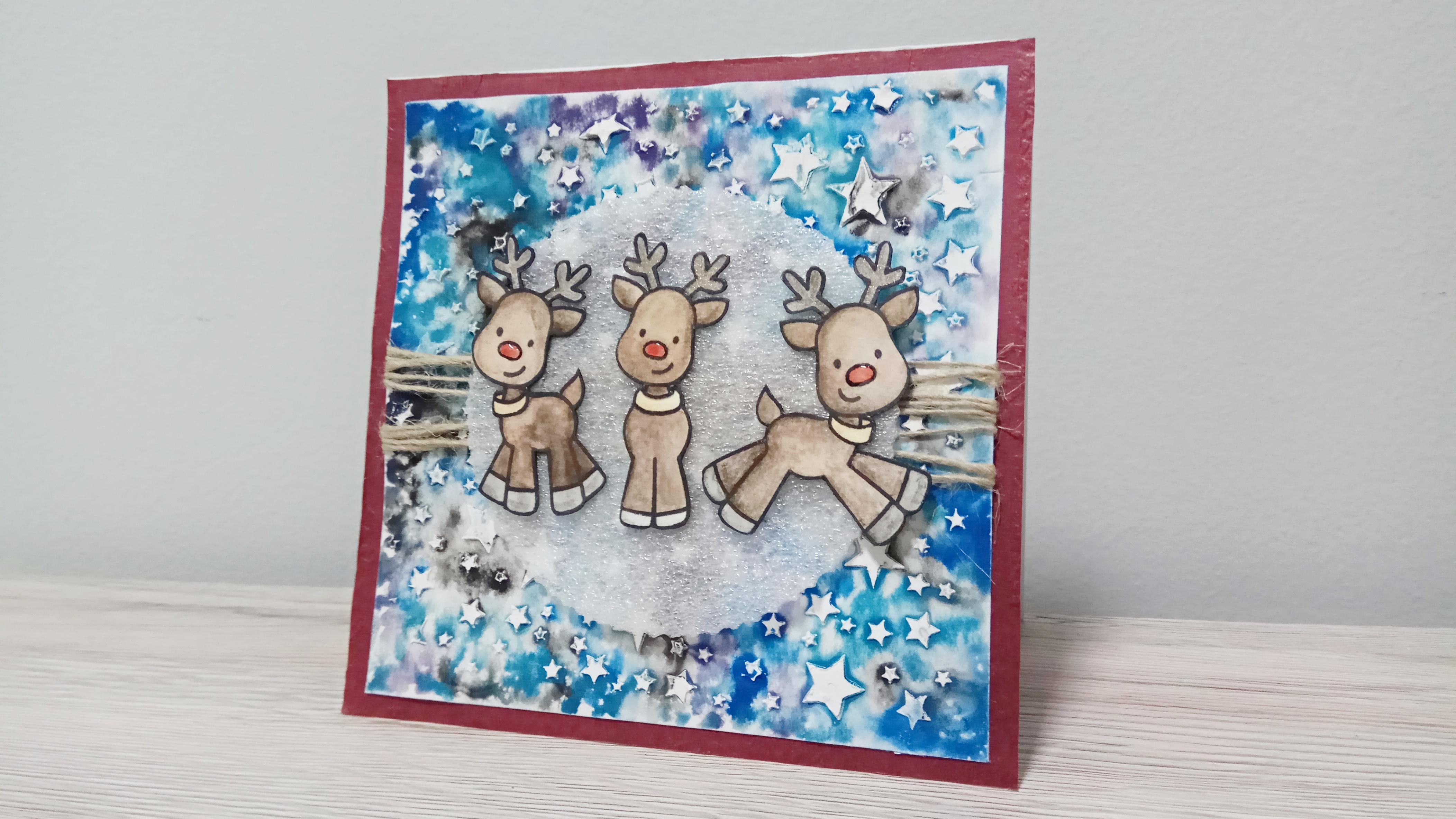 Card natalizia con renne su cielo stellato