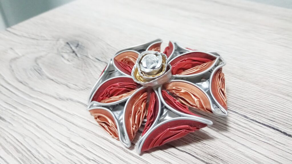 Spilla fiore con petali triangolari sui toni del rosso e del rosa