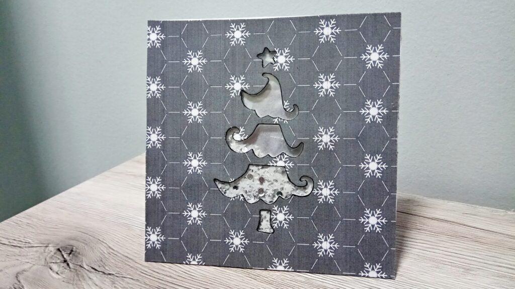 Shaker Card natalizia con albero su base grigia con fiocchi di neve stilizzati