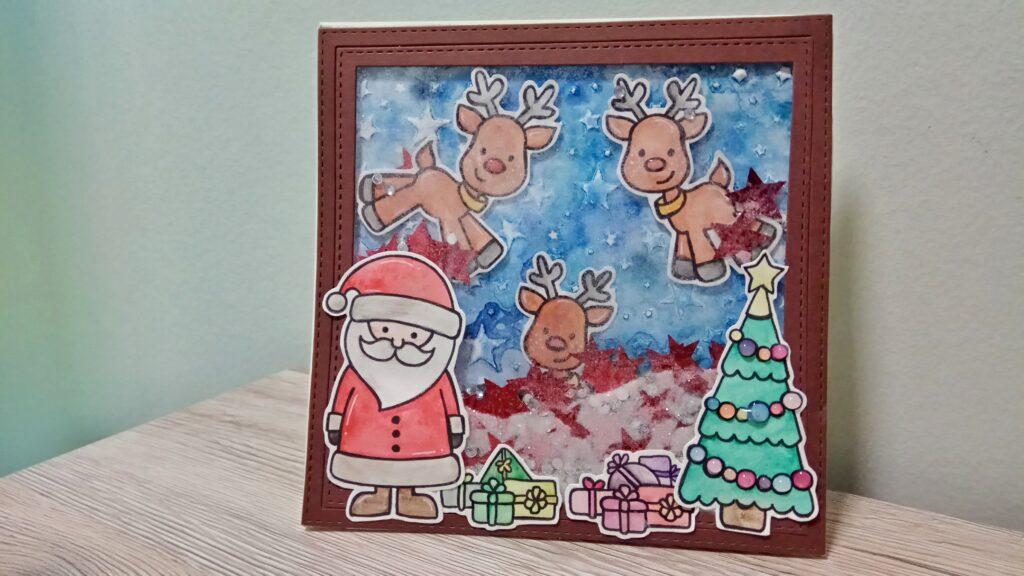 Shaker Card natalizia con Babbo Natale e renne che consegnano i regali